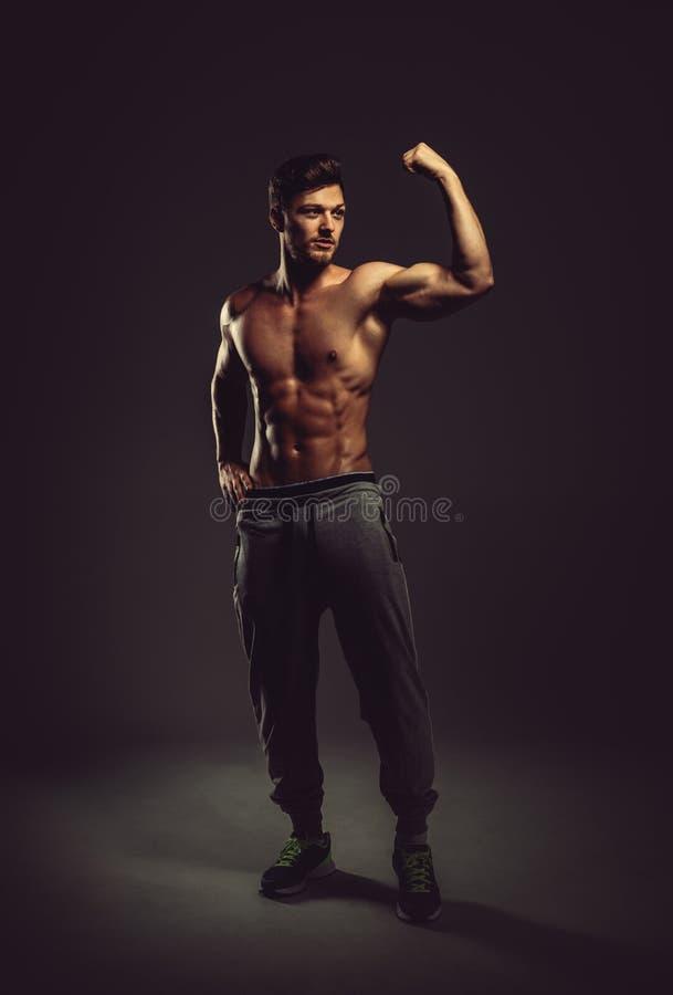 显示二头肌肌肉的运动英俊的人 库存图片