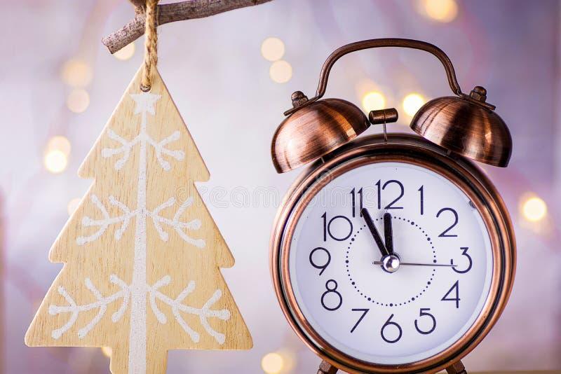显示五分钟的葡萄酒铜闹钟对午夜 读秒新年度 垂悬在分支的木圣诞树装饰品 免版税库存图片