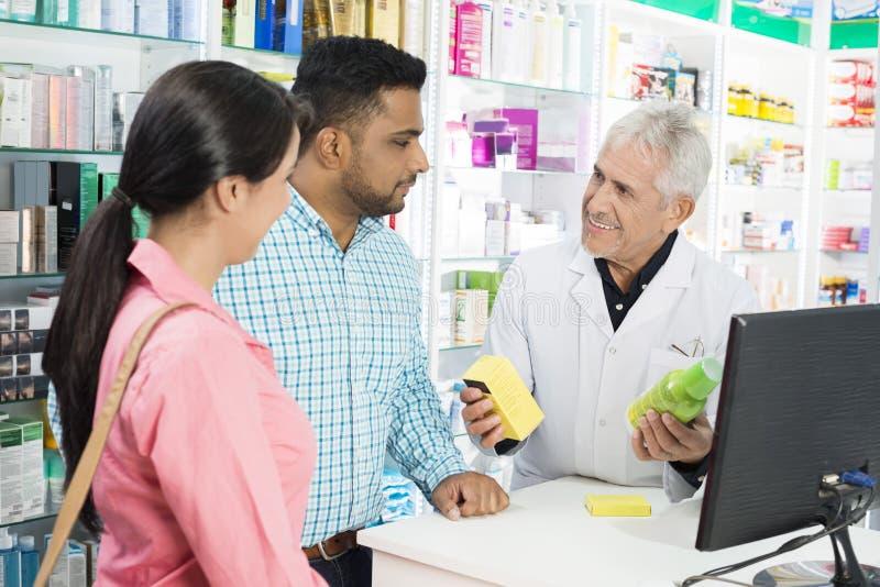 显示产品的药剂师对夫妇在结算台 库存图片