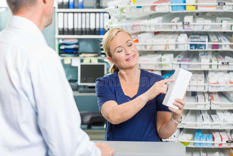 显示产品的细节药剂师对顾客在药房 免版税库存照片