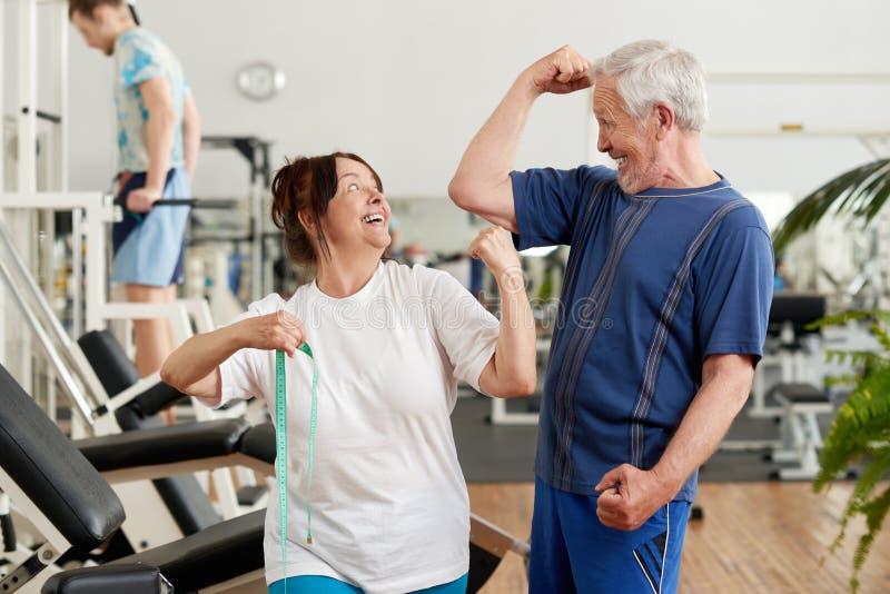显示他们的二头肌的快乐的资深夫妇在健身房 免版税图库摄影