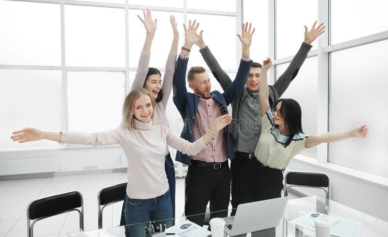 显示他们的成功的愉快的企业队在桌面附近 免版税库存照片