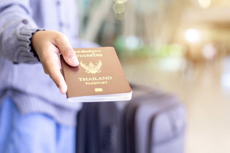 显示他们的泰国护照的旅客在机场 图库摄影