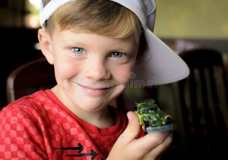 显示他新的玩具汽车的愉快的微笑的男孩 库存图片