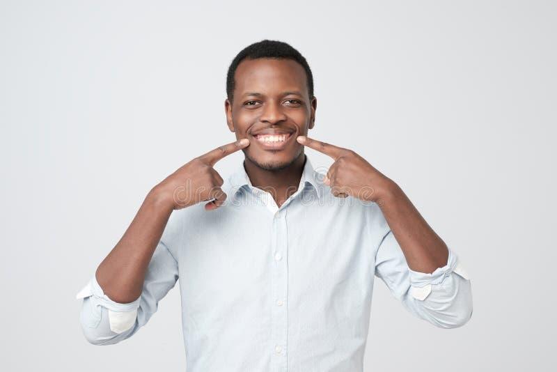 显示他的优秀白色牙的非洲年轻帅哥 免版税库存照片