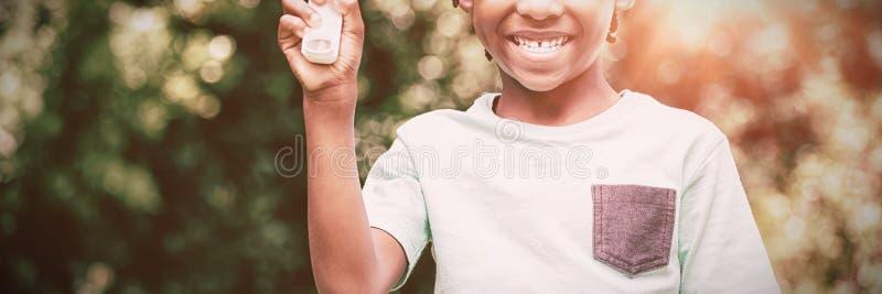 显示他的哮喘吸入器的男孩 库存图片