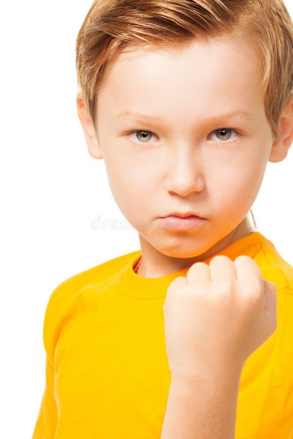 显示他的拳头的坏脾气的孩子 库存图片