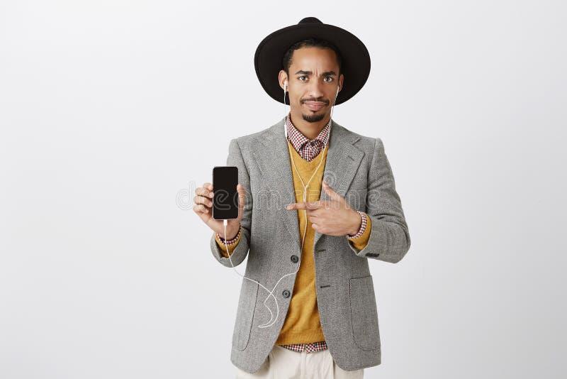显示令人厌恶的事的生气的人在智能手机 失望的悦目时髦的人画象黑帽会议的 免版税库存照片