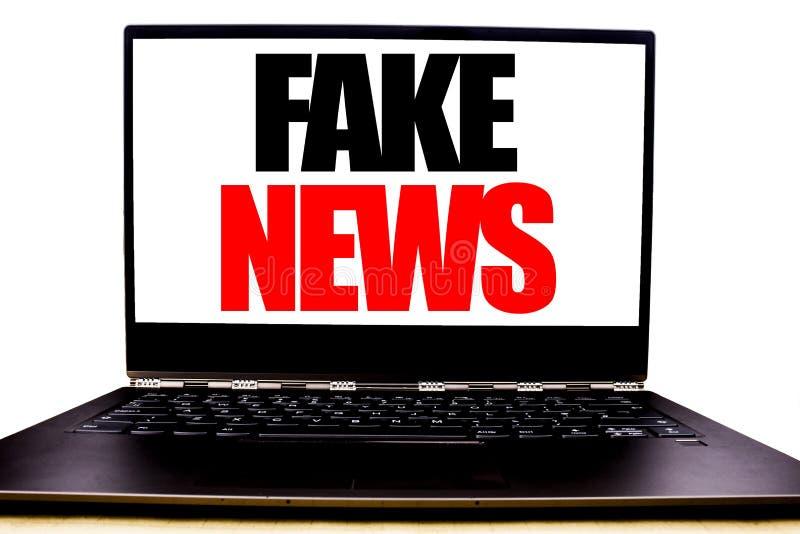 显示假新闻的手写的文本 企业在显示器前面屏幕写的骗局新闻事业的概念文字,白色背景 免版税库存图片