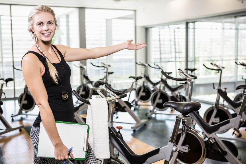 显示健身房的微笑的女性教练员 免版税库存图片