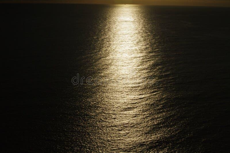 显示光的条纹在海洋的令人毛骨悚然的日落 免版税库存图片