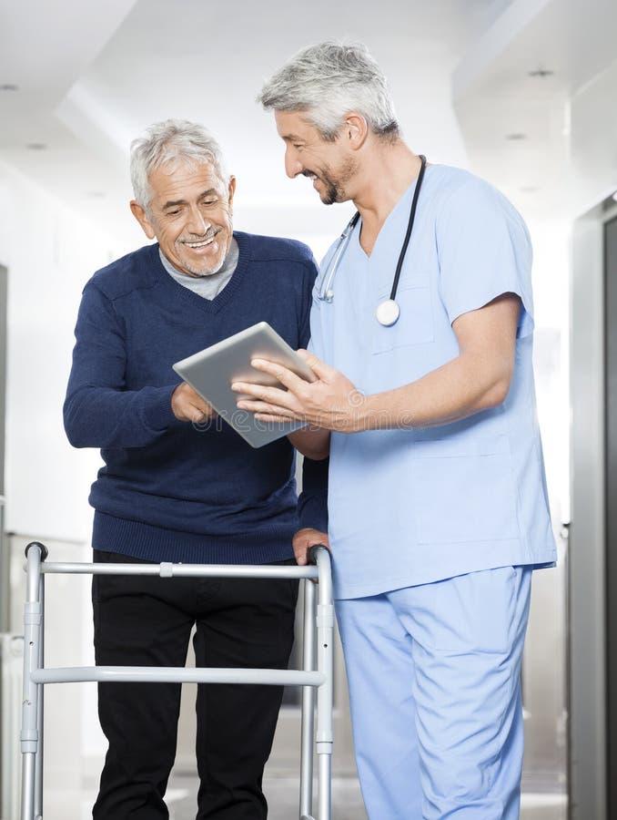 显示关于片剂计算机的生理治疗师报告对老人 库存照片