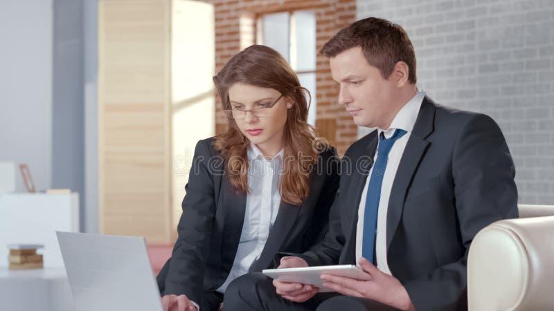 显示关于膝上型计算机,上司的女性秘书报告为业务会议做准备 免版税库存照片