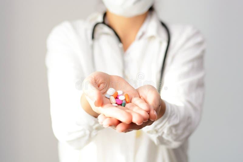 显示几个片剂和药片在她的棕榈的一位女性医生的播种的射击 库存图片