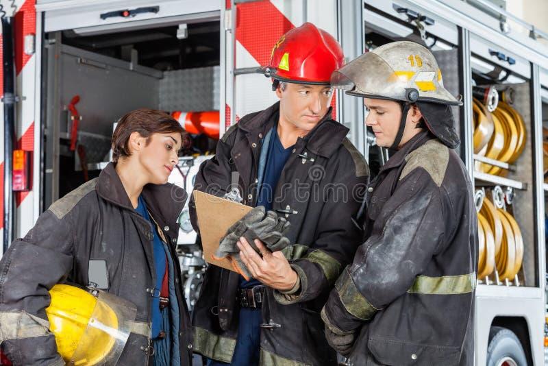 显示剪贴板的消防队员对同事 图库摄影