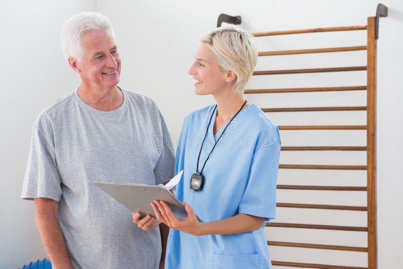 显示剪贴板的治疗师对老人 免版税库存照片