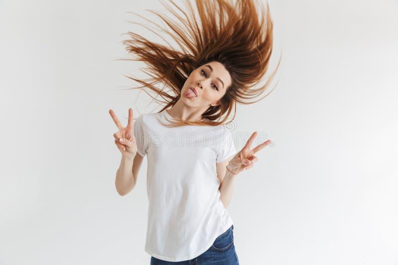 显示和平姿态和她的舌头的T恤杉的滑稽的妇女 免版税库存照片