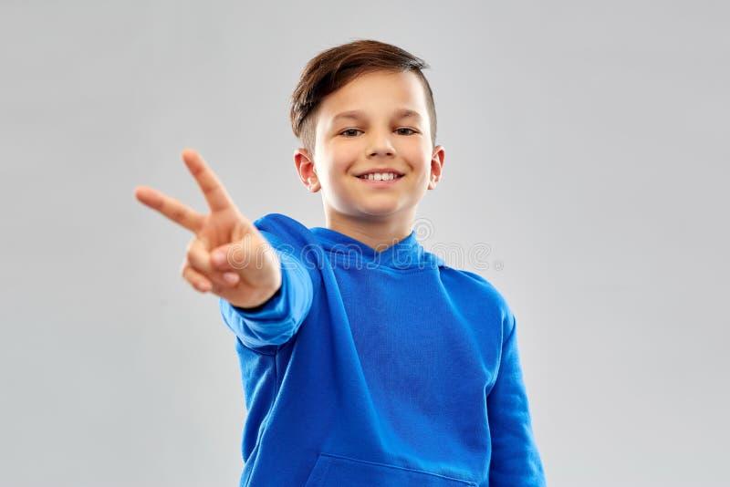 显示和平姿态的蓝色有冠乌鸦的微笑的男孩 图库摄影