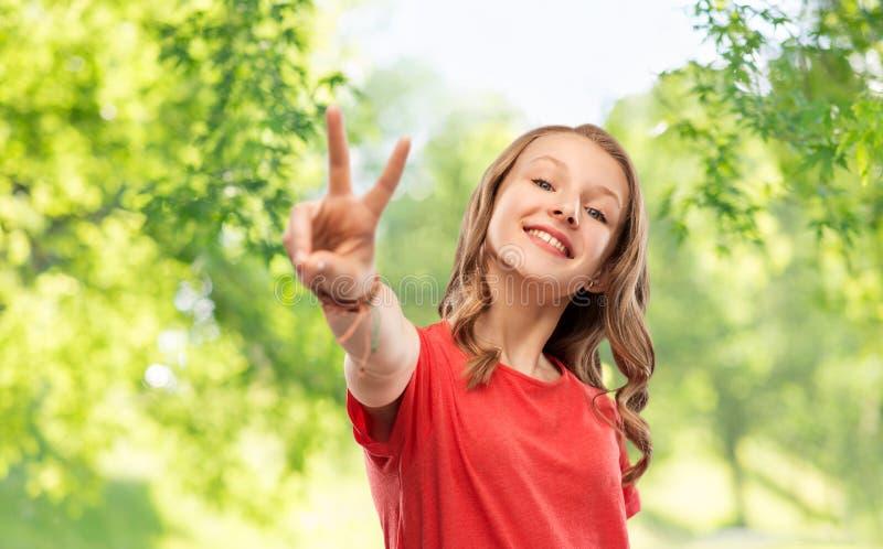 显示和平的红色T恤杉的微笑的十几岁的女孩 库存照片