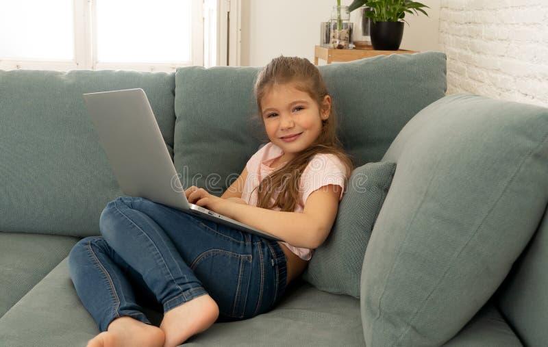 显示和浏览膝上型计算机的美丽的逗人喜爱的迷人的女孩互联网在家微笑 免版税库存照片