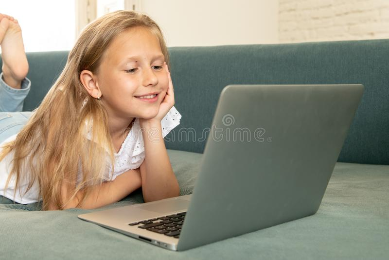 显示和浏览膝上型计算机的美丽的逗人喜爱的迷人的矮小的白肤金发的女孩互联网微笑和在家躺下在长沙发 库存图片