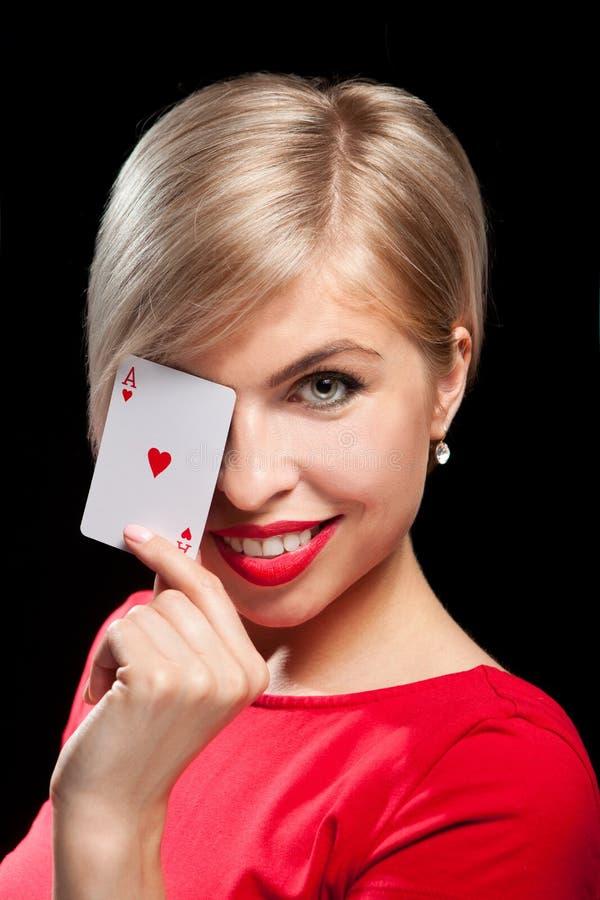 显示啤牌卡片的美丽的白肤金发的女孩 免版税库存图片