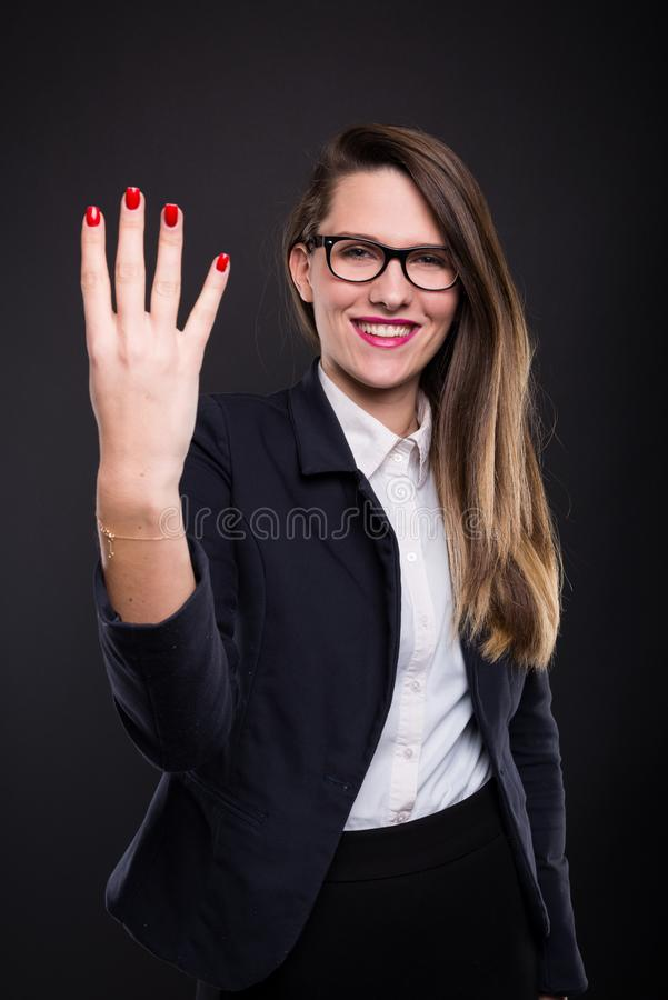 显示四个手指的美丽的聪明的女孩 库存图片
