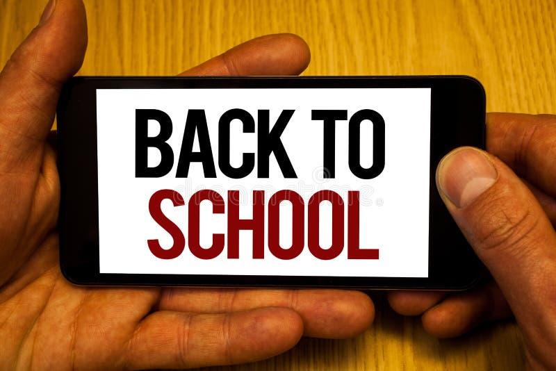 显示回到学校的文本标志 概念性照片回归到到达类第一的天研究教室举行黑色的两只手 免版税库存照片
