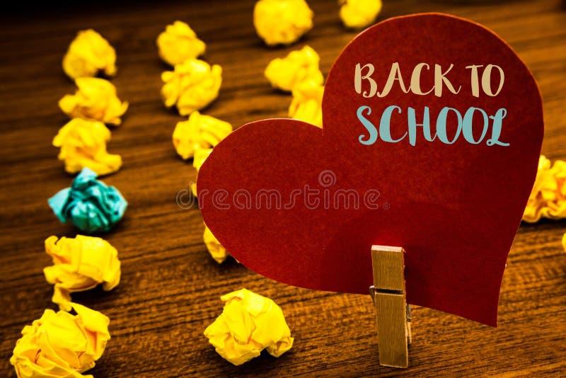 显示回到学校的文本标志 概念性照片回归到类第一天研究教室到达的文本红色心脏木头cli 库存照片