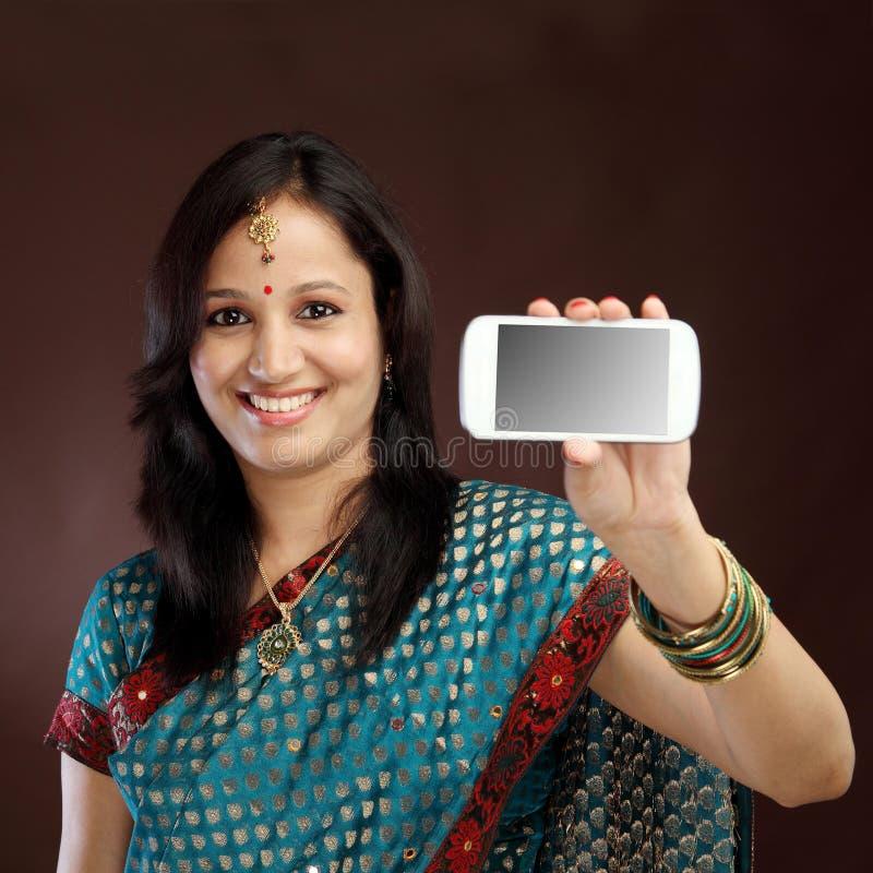 显示图片的她自己的微笑的年轻传统妇女 免版税库存照片