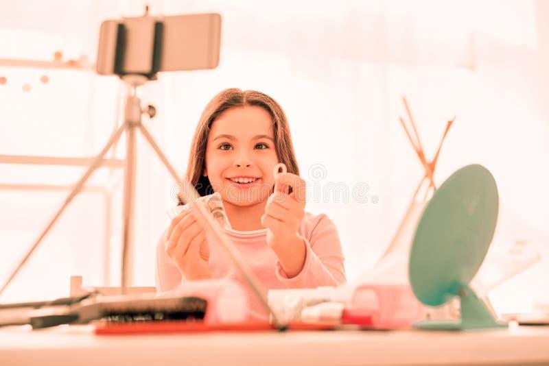 显示圆环的快乐的愉快的女孩对照相机 免版税图库摄影