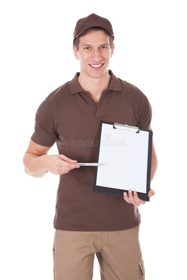 显示在剪贴板的年轻愉快的送货人形式 库存图片
