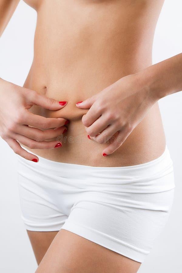 显示在她的腹部的妇女脂肪团 库存照片
