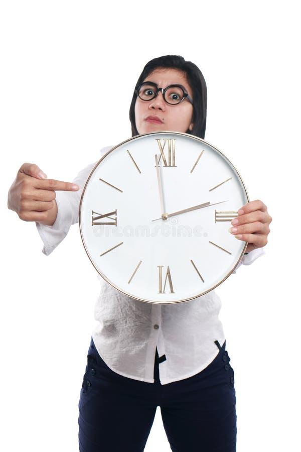 显示在时钟的疯狂的亚裔女实业家时间 免版税库存照片