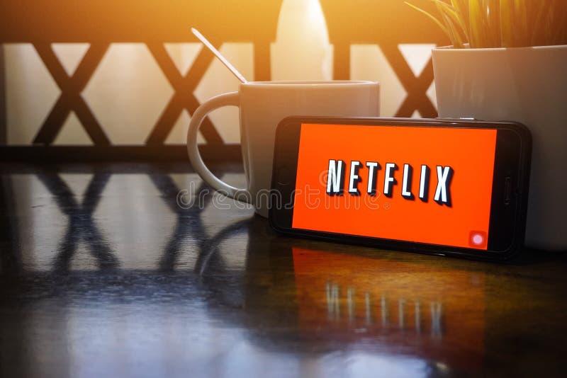显示在木桌上的智能手机词Netflix与选择聚焦和庄稼片段 免版税库存照片
