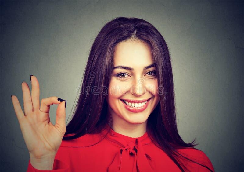 显示在灰色背景的笑的少妇好标志 免版税库存图片