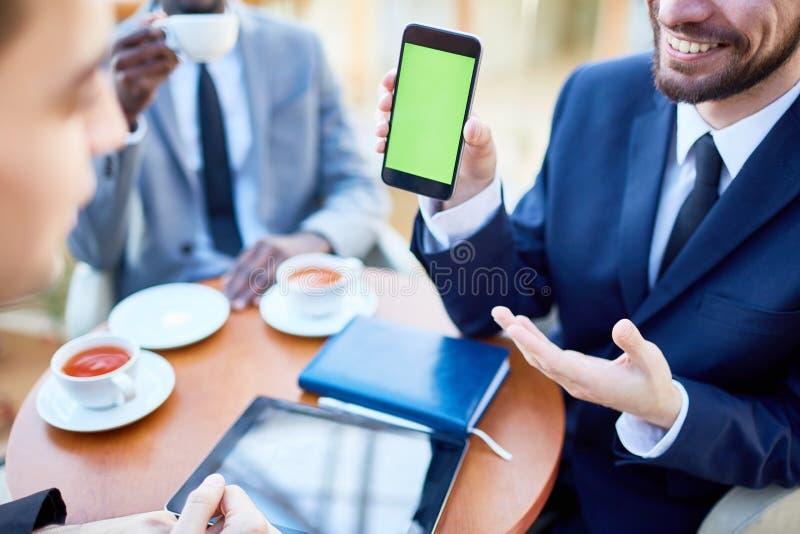 显示在电话的微笑的商人流动应用 免版税图库摄影