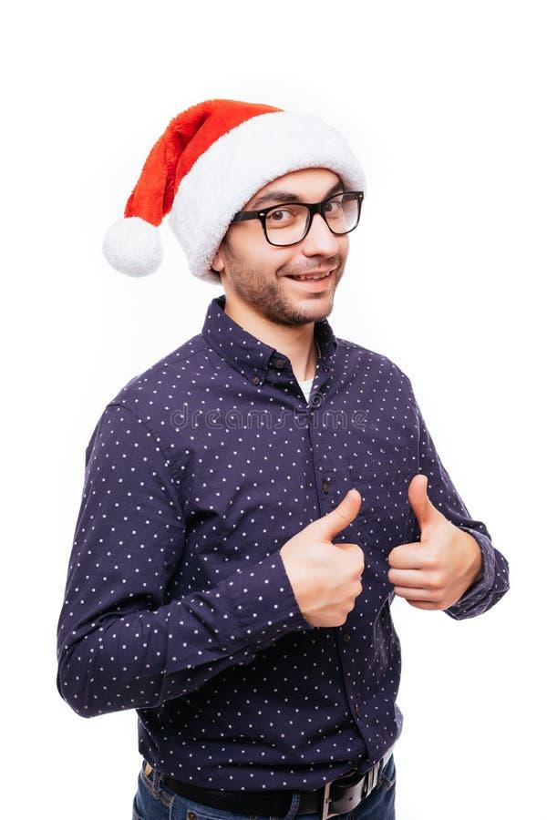 显示在白色的英俊的商人穿戴圣诞老人帽子赞许隔绝了背景 免版税库存照片