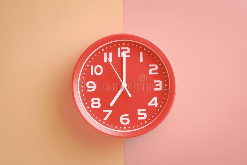 显示在米黄桃红色背景的红色时钟7点 库存照片
