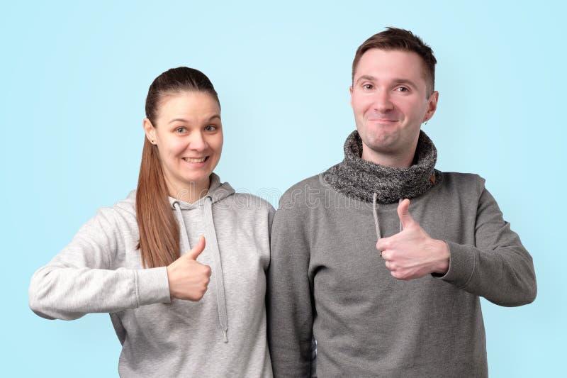 显示在蓝色背景的愉快的年轻夫妇赞许 图库摄影
