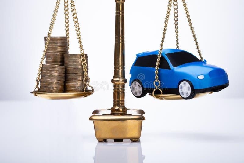 显示在被堆积的硬币和汽车之间的正义标度平衡 库存图片