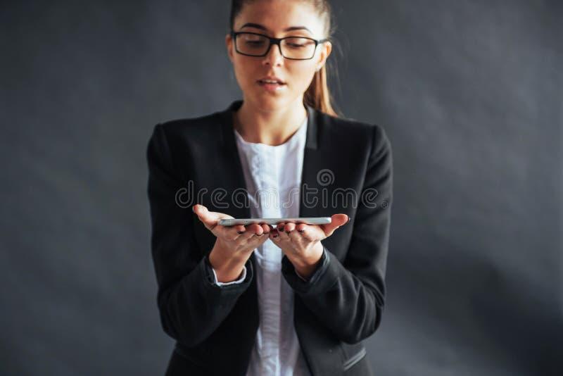 显示在黑背景的快乐的妇女画象一个智能手机 在智能手机的焦点在手中 库存图片