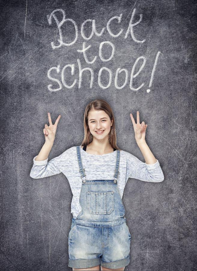 显示在黑板背景的少年女孩胜利标志 库存图片
