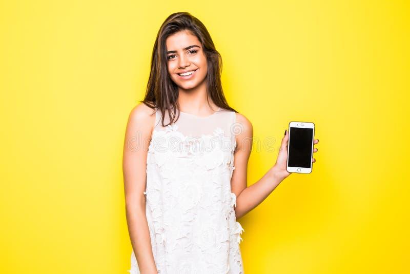 显示在黄色背景的一名快乐的妇女的画象空白的智能手机屏幕 库存图片