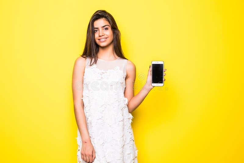 显示在黄色背景的一名快乐的妇女的画象空白的智能手机屏幕 库存照片