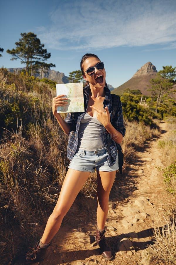 显示地图的激动的少妇远足者 免版税库存图片