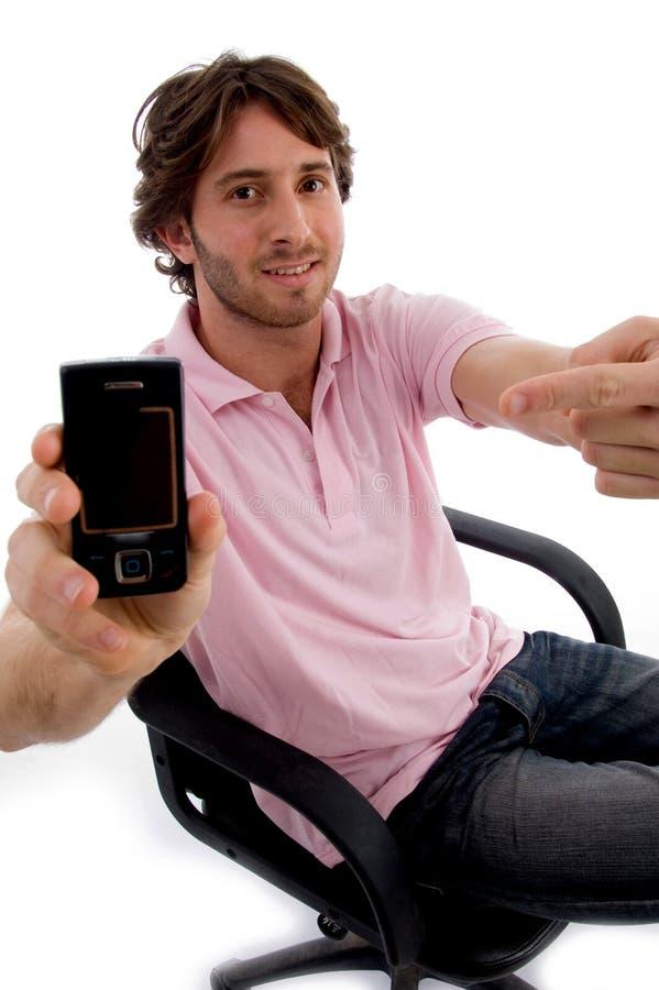 显示坐的年轻人的男性移动电话 库存照片