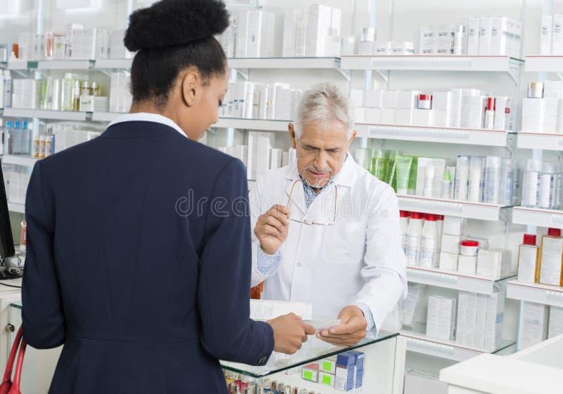 显示处方的女实业家对化学家在药房 图库摄影