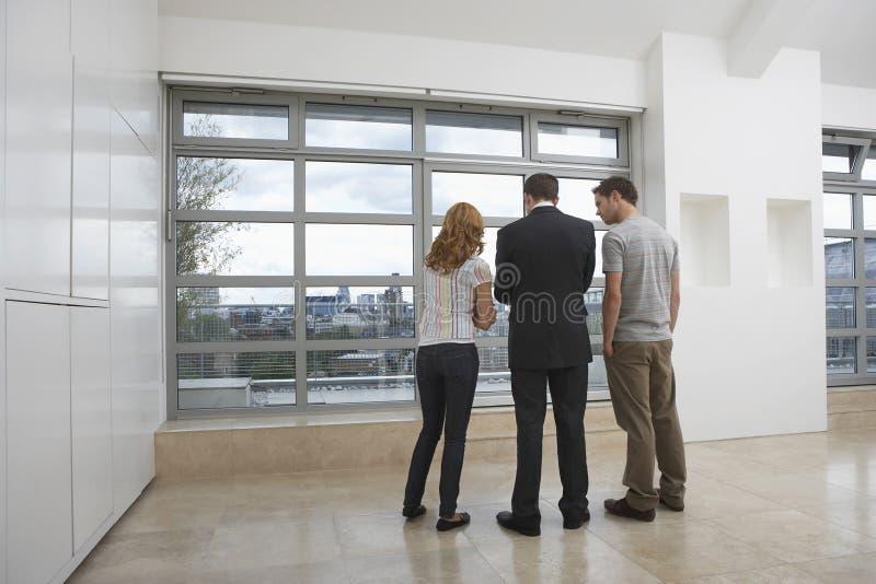 显示夫妇新的公寓的房地产开发商 免版税图库摄影