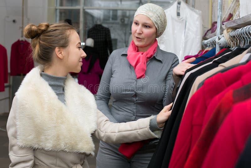 显示夹克的品种女售货员对顾客在零售店 免版税库存照片